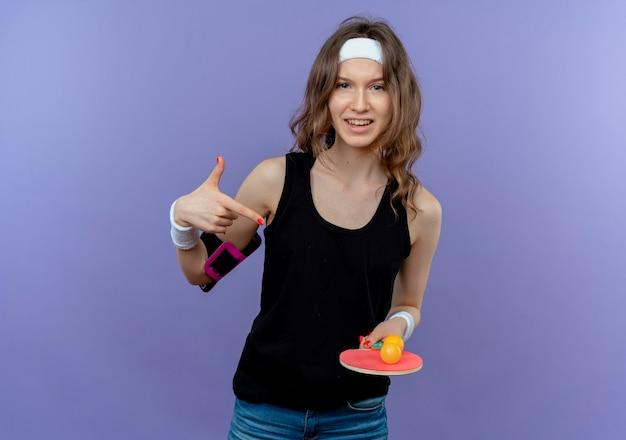 Jovem garota fitness em roupa esportiva preta com tiara segurando uma raquete e bolas para tênis de mesa apontando com o dedo, parecendo confiante em pé sobre a parede azul