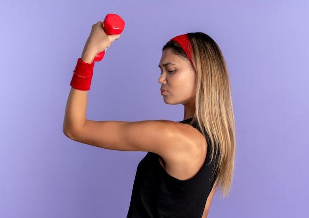 Jovem garota fitness em roupa esportiva preta e bandana vermelha, malhando com halteres mostrando bíceps parecendo confiante sobre o azul