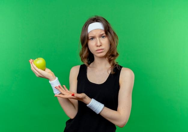 Jovem garota fitness em roupas esportivas pretas com fita para a cabeça, segurando uma maçã verde, apresentando o braço da mão em pé sobre a parede verde