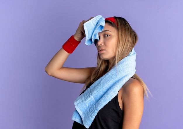 Jovem garota fitness em roupas esportivas pretas e bandana vermelha com fones de ouvido, enxugando a testa com uma toalha em pé sobre a parede azul