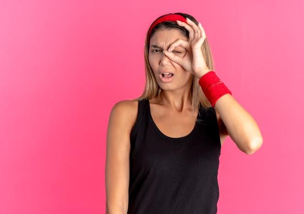 Jovem garota fitness em roupas esportivas pretas e bandana vermelha fazendo sinal de ok olhando para a câmera através deste canto com expressão confusa em pé sobre a parede rosa
