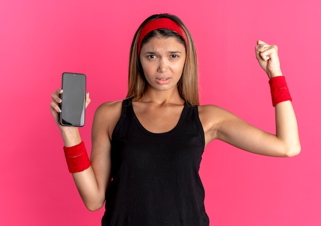 Jovem garota fitness em roupas esportivas pretas e bandana vermelha, mostrando o punho cerrado do smartphone com cara de raiva em pé sobre a parede rosa