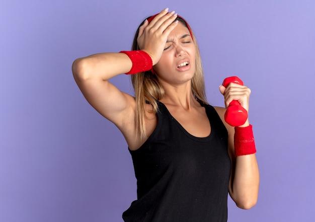 Jovem garota fitness em roupas esportivas pretas e bandana vermelha segurando halteres, parecendo cansada e exausta com hnad na cabeça sobre azul