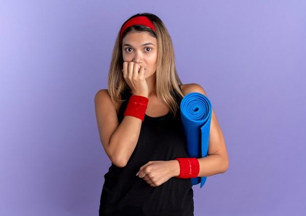 Jovem garota fitness em roupas esportivas pretas e bandana vermelha segurando um tapete de ioga, parecendo estressada e nervosa roendo as unhas em pé sobre a parede azul