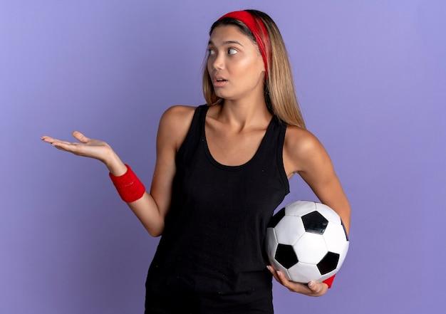 Jovem garota fitness em roupas esportivas pretas e bandana vermelha, segurando uma bola de futebol, apresentando spmething com o braço da mão preocupada em pé sobre a parede azul