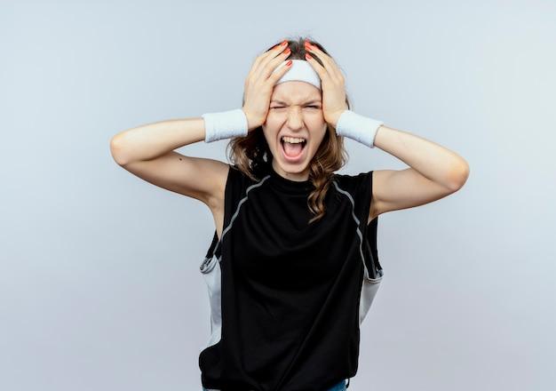 Jovem garota fitness em um sportswear preto com bandana enlouquecida segurando a cabeça dela gritando em pé sobre uma parede branca