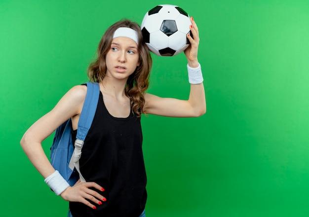 Jovem garota fitness em um sportswear preto com mochila e bandana segurando uma bola de futebol sobre a cabeça lookign de lado confusa em pé sobre a parede verde