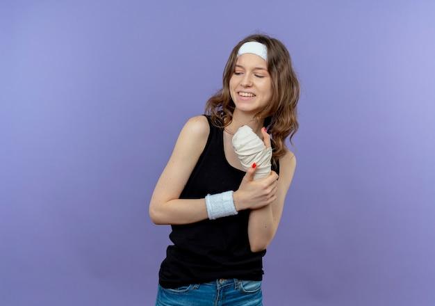 Jovem garota fitness em um sportswear preto com uma faixa na cabeça tocando seu pulso enfaixado, parecendo confusa em pé sobre a parede azul