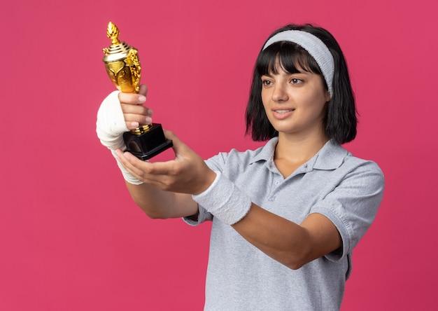 Jovem garota fitness usando bandana e mão enfaixada segurando um troféu, olhando para ela feliz e sorrindo satisfeita