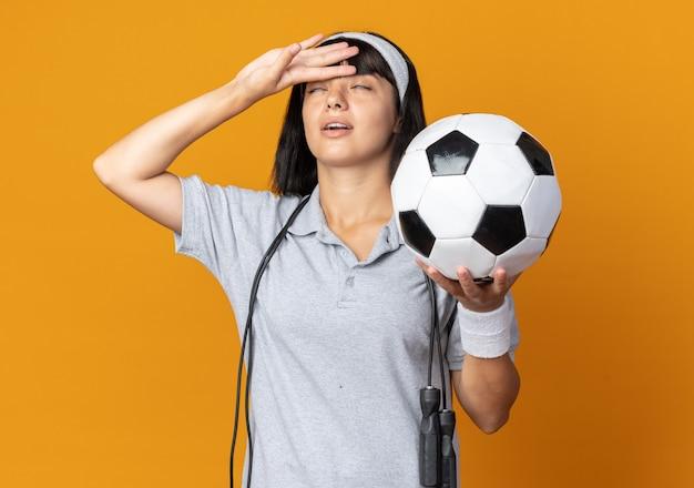 Jovem garota fitness usando bandana e pular corda em volta do pescoço segurando uma bola de futebol, parecendo cansada e sobrecarregada com a mão na testa em pé sobre um fundo laranja