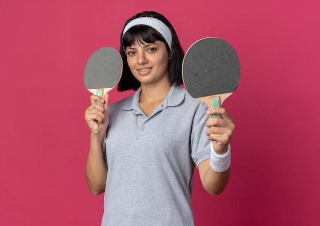 Jovem garota fitness usando bandana segurando raquetes de tênis de mesa, olhando para a câmera com um sorriso no rosto em pé sobre um fundo rosa
