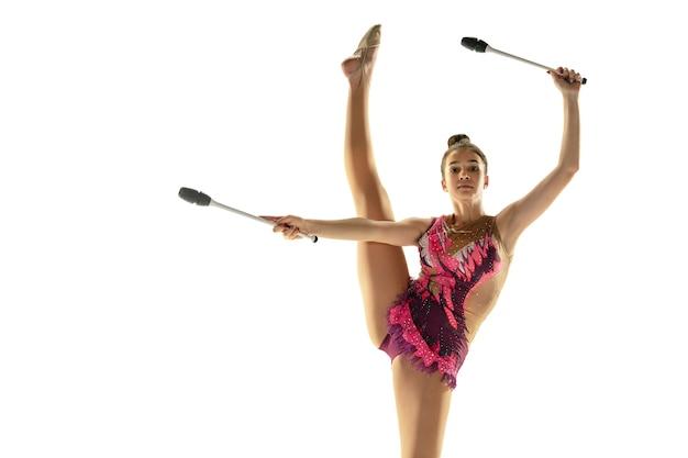 Jovem garota flexível isolada na parede branca. modelo feminino adolescente como artista de ginástica rítmica praticando com equipamentos. exercícios de flexibilidade, equilíbrio. graça em movimento, esporte.