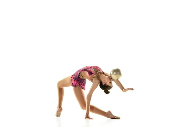 Jovem garota flexível isolada no fundo branco do estúdio. modelo feminino adolescente como artista de ginástica rítmica praticando com equipamentos. exercícios de flexibilidade, equilíbrio. graça em movimento, esporte.