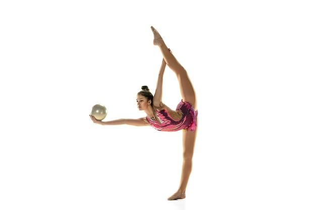 Jovem garota flexível isolada no fundo branco. modelo feminino adolescente como artista de ginástica rítmica praticando com equipamentos.