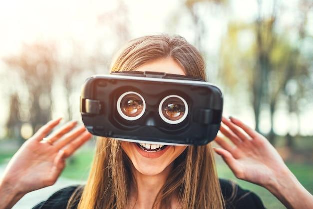 Jovem garota gosta de óculos de realidade virtual ao ar livre