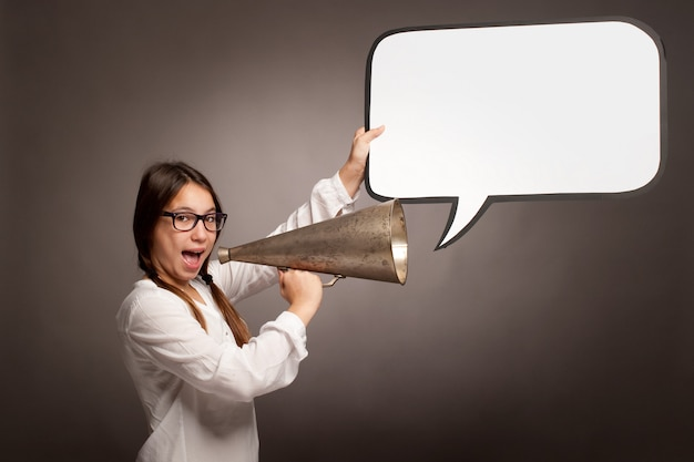 Jovem garota gritando com um megafone antigo sobre um fundo cinza