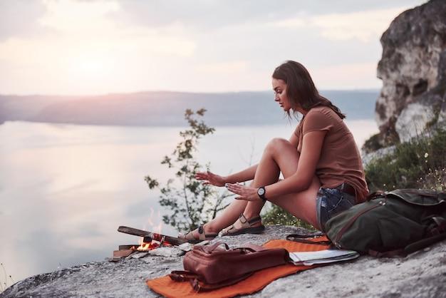 Jovem garota hippie com mochila, apreciando o pôr do sol no pico da montanha de pedra.