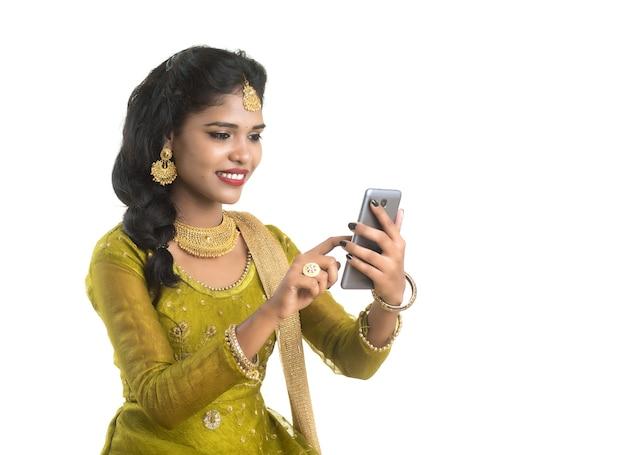 Jovem garota indiana tradicional usando um celular ou smartphone isolado em uma parede branca