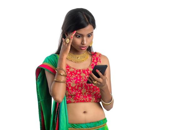 Jovem garota indiana tradicional usando um celular ou smartphone isolado