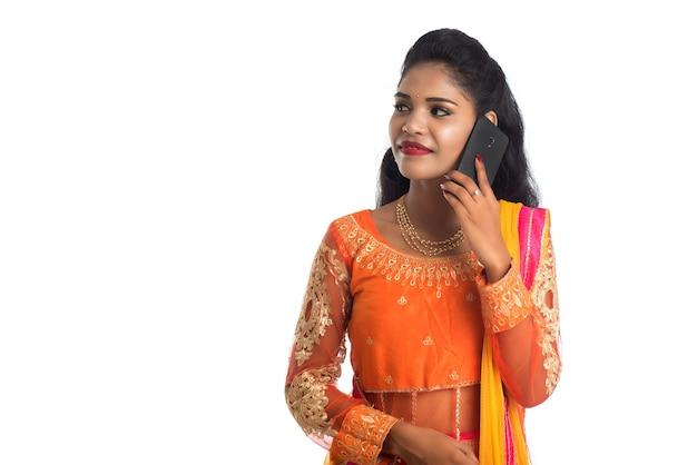 Jovem garota indiana tradicional usando um telefone celular ou smartphone em branco