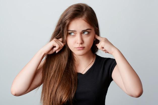 Jovem garota irritada na camisa preta, furando os dedos nas orelhas