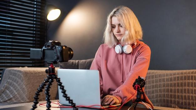 Jovem garota loira criadora de conteúdo com fones de ouvido trabalhando em seu laptop na mesa com a câmera