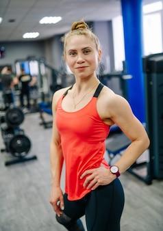 Jovem garota loira linda fitness treina em uma academia em um equipamento de esporte. a menina está olhando para a câmera.