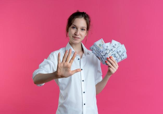 Jovem garota loira russa satisfeita gesticulando cinco segurando dinheiro rosa com espaço de cópia