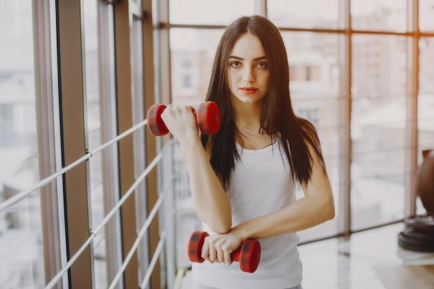 Jovem, garota magra em uma camisa branca e legging cinza em pé em um ginásio com halteres vermelho