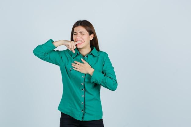 Jovem garota mordendo o dedo indicador, segurando a mão sobre o peito em uma blusa verde, calça preta e parecendo exausta. vista frontal.
