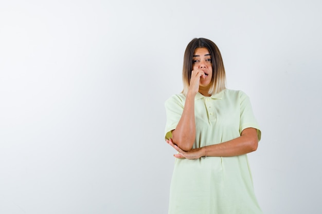 Jovem garota mordendo os dedos emocionalmente, segurando a mão sob o cotovelo na camiseta e parecendo assustada. vista frontal.