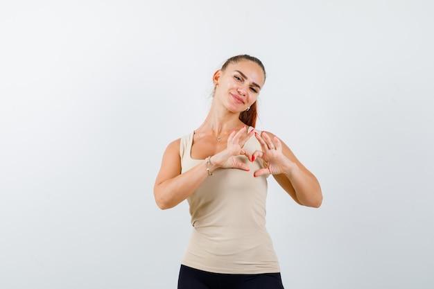 Jovem garota mostrando forma de coração com as mãos na calça bege, blusa preta e olhando feliz, vista frontal.