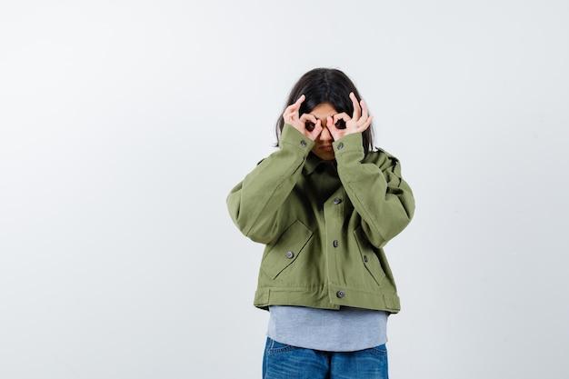 Jovem garota mostrando gesto de binóculos em suéter cinza, jaqueta cáqui, calça jeans e olhar bonito, vista frontal.