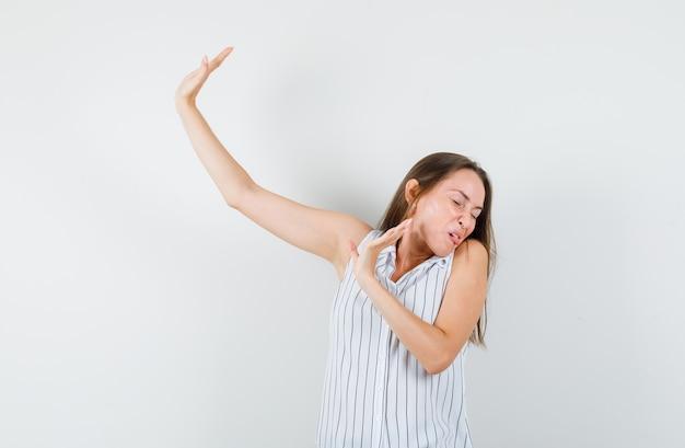 Jovem garota mostrando o gesto de parar enquanto vira a cabeça em uma camiseta e parece enojada vista frontal.