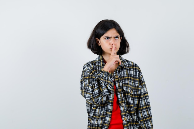 Jovem garota mostrando o gesto de silêncio na camisa e camiseta vermelha e olhando com raiva, vista frontal.