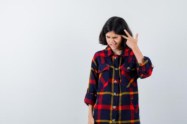 Jovem garota mostrando o símbolo da paz perto do olho, fechando os olhos em uma camisa xadrez e parecendo exausta. vista frontal.