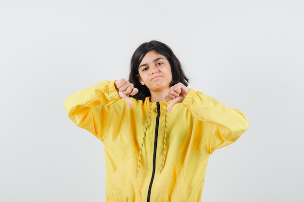 Jovem garota mostrando os polegares para baixo com as duas mãos na jaqueta amarela e parecendo descontente.