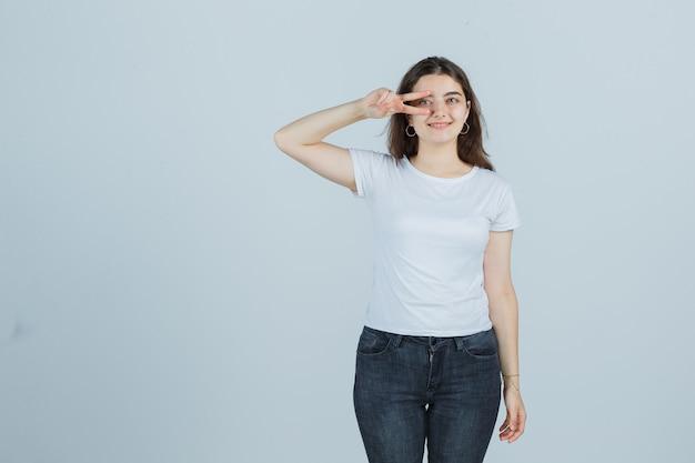 Jovem garota mostrando sinal de vitória no olho em t-shirt, jeans e olhando feliz, vista frontal.