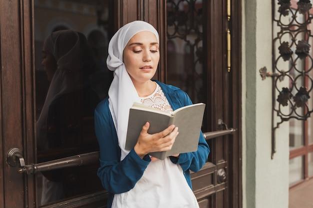 Jovem garota muçulmana usa hijab com o livro de diário do estudante islâmico e o conceito de conhecimento