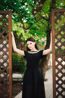 Jovem garota muito sexy elegante de vestido preto ao ar livre em um dia ensolarado.