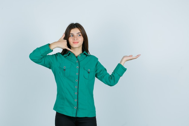 Jovem garota na blusa verde, calça preta, mostrando o gesto do telefone, espalhando a palma da mão para o lado e parecendo otimista, vista frontal.