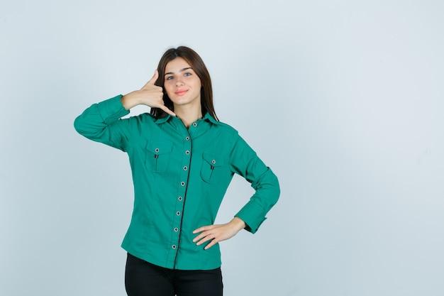 Jovem garota na blusa verde, calça preta, mostrando o gesto do telefone, segurando a mão no quadril e olhando otimista, vista frontal.