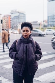Jovem garota negra e encaracolada na rua