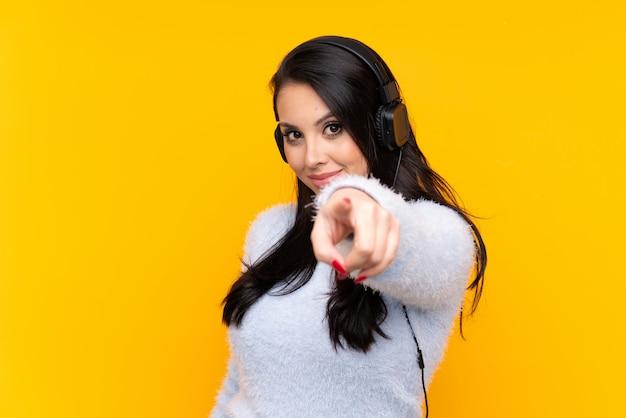Jovem garota ouvindo música de parede amarela e apontando para a frente