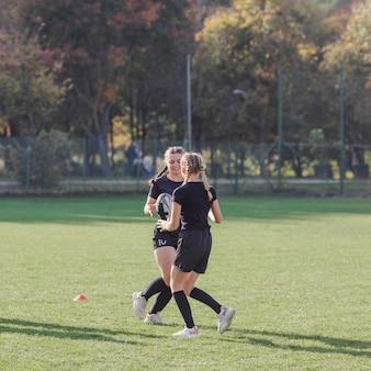 Jovem garota passando uma bola de rugby