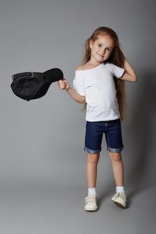 Jovem garota posando em um fundo cinza, emoções alegres brilhantes no rosto da garota, a criança caretas e poses. rússia, sverdlovsk, 12 de agosto de 2018
