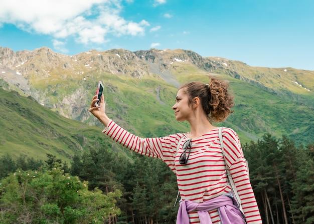 Jovem garota procurando uma conexão no topo da colina de montanhas com vista perfeita.