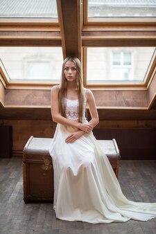 Jovem garota romântica e elegante em um longo vestido branco sentada no baú dote no loft