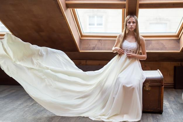 Jovem garota romântica e elegante em um vestido longo branco flutuante sentada no baú dote no loft