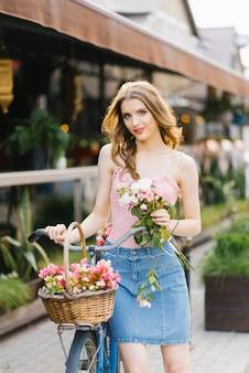 Jovem garota romântica fica e segura uma bicicleta com uma cesta de flores em um verão ensolarado